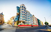 26 may 2018: Red tram passing in front of Dancing House building in Prague. Czech Republic