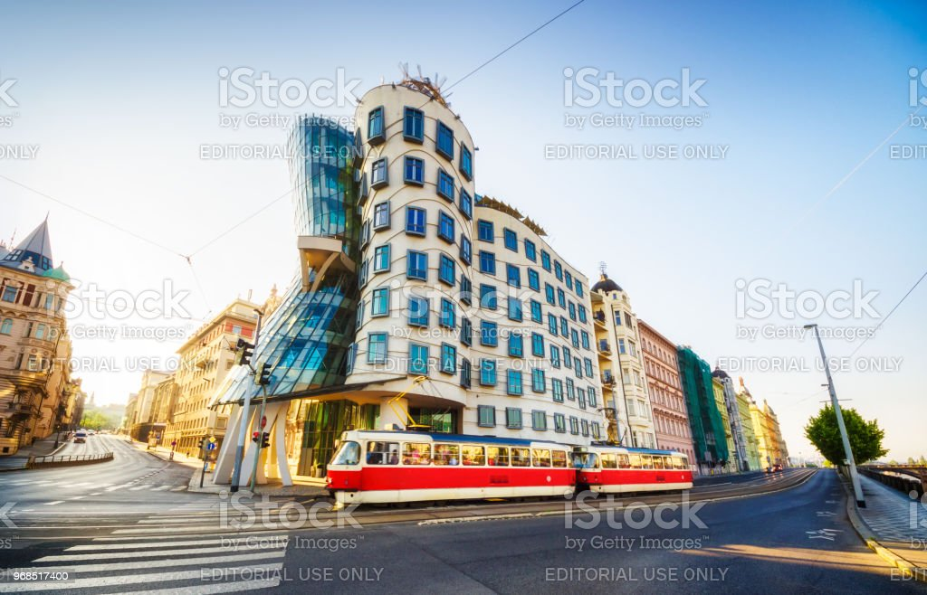 red tram in front of Dancing House (Tančící dům) in the morning. Prague stock photo