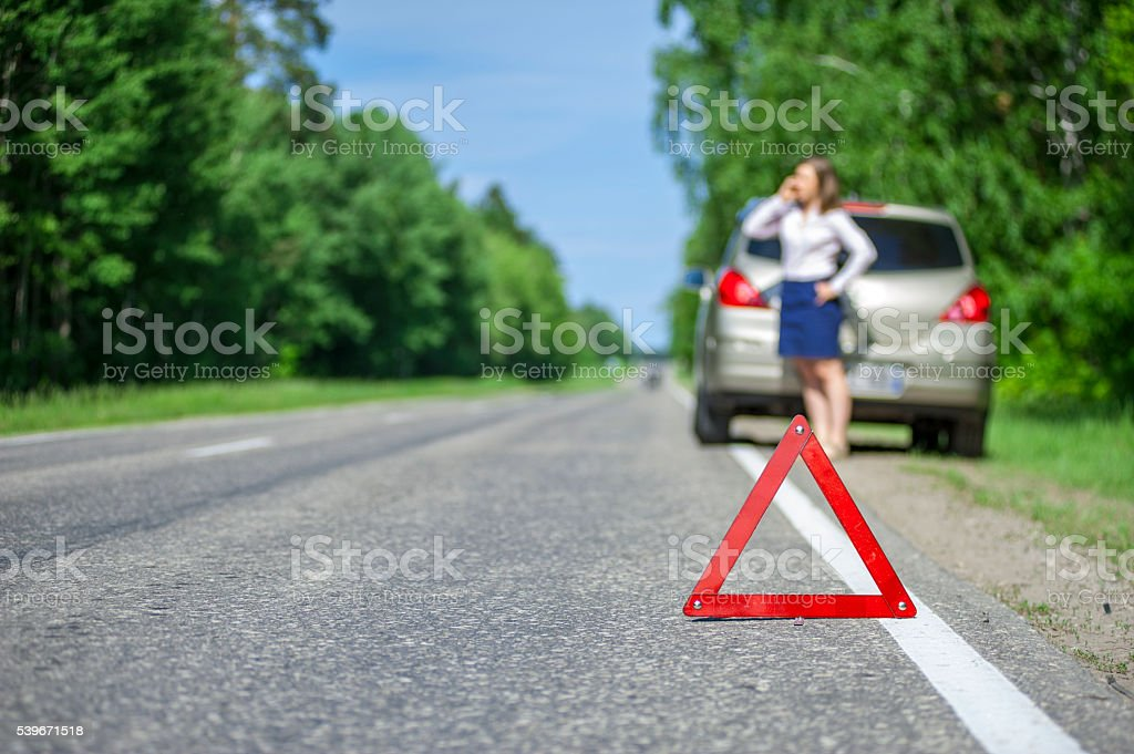 Red triangle sign on the road and Young woman stock photo
