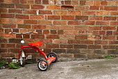 Red tricycle parked next to a brick wall.