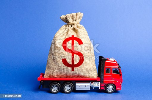 istock Red truck carries a big bag of money. Attracting investment in development and modernization of production and business projects. Revenue profit. super profit. corruption schemes. Financial groups 1163887548
