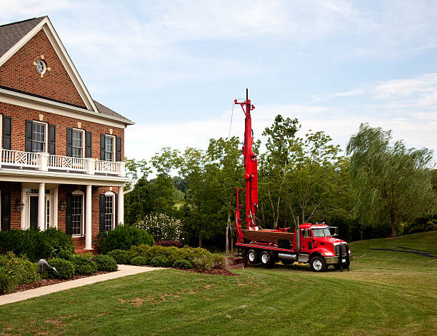 red truck drilling into the yard - drill stock photos and pictures