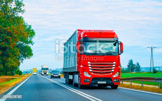 Truck in summer road of Poland. Trucker in highway. Lorry doing logistics work. Semi trailer with driver. Big cargo car drive. Freight delivery. Transport export industry. Container with goods