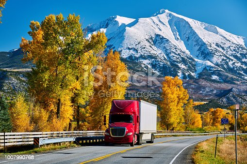 Red truck on highway in Colorado at autumn, USA. Mount Sopris landscape.