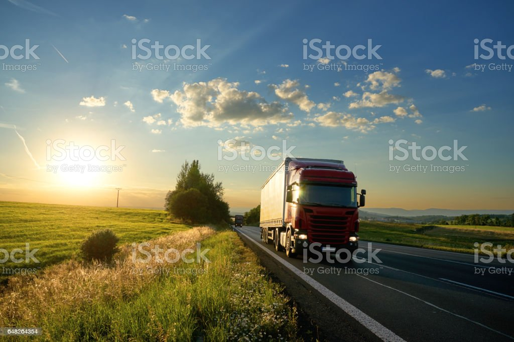 Red truck on the road in a landscape at sunset stock photo