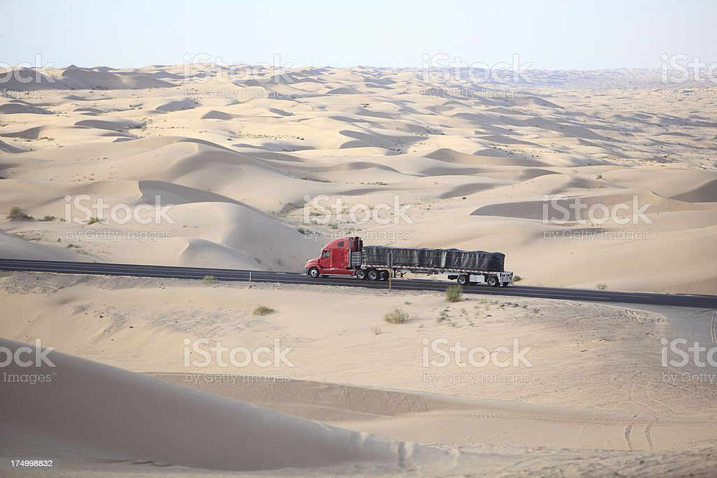 Red Truck Traveling The Imperial Valley Sand Dunes stock photo