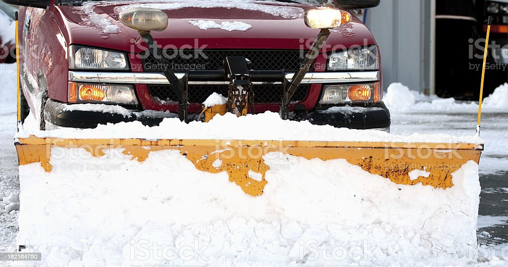 red truck with snow plow clearing pavement stock photo