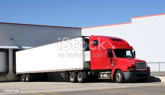 Tractor trailer sitting at a loading dock.  Space for text on the trailer.