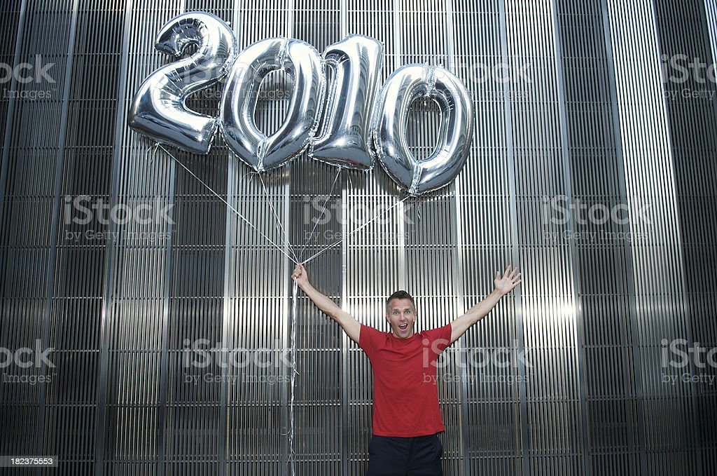 Red T-Shirt Guy Holds Shiny Silver 2010 Balloons stock photo