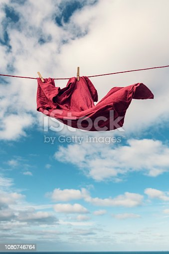 Red t-shirt on a washing line blowing in strong wind.