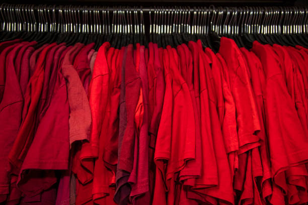 Red T-shirts on hangers on a shop wardrobe closet rail Red T-shirts on hangers on a shop wardrobe closet rail red shirt stock pictures, royalty-free photos & images