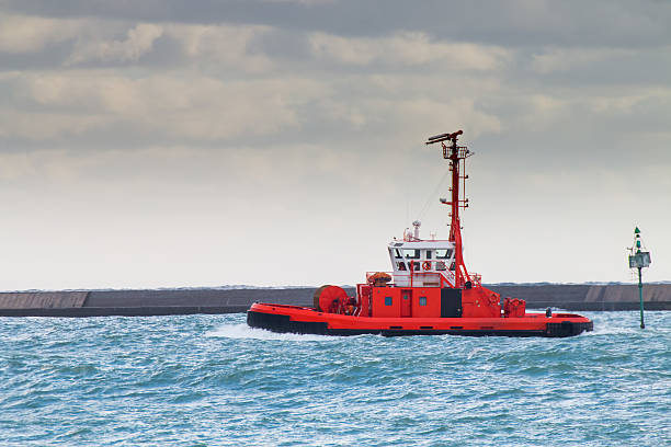 red tugboat navigates in port  waiting for a ship red tugboat navigates in port in a cloudy day waiting for a ship deadweight stock pictures, royalty-free photos & images