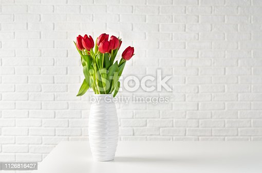 Red tulips in white vase against white bricks background. Copy space