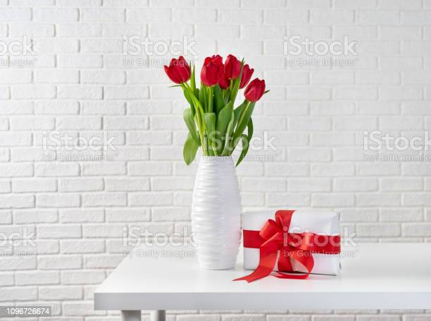 Red tulips in white vase next to a gift box with red ribbon picture id1096726674?b=1&k=6&m=1096726674&s=612x612&h=izzajjijpe1hay7ltwstgoratyuwnq88gtffylvynm4=