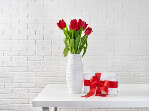 Red tulips in white vase next to a gift box with red ribbon picture id1096726674?b=1&k=6&m=1096726674&s=612x612&w=0&h=uewnx0xpbjgi9kxh18ohdvanmmbgqd0d6vpwj4ew bu=