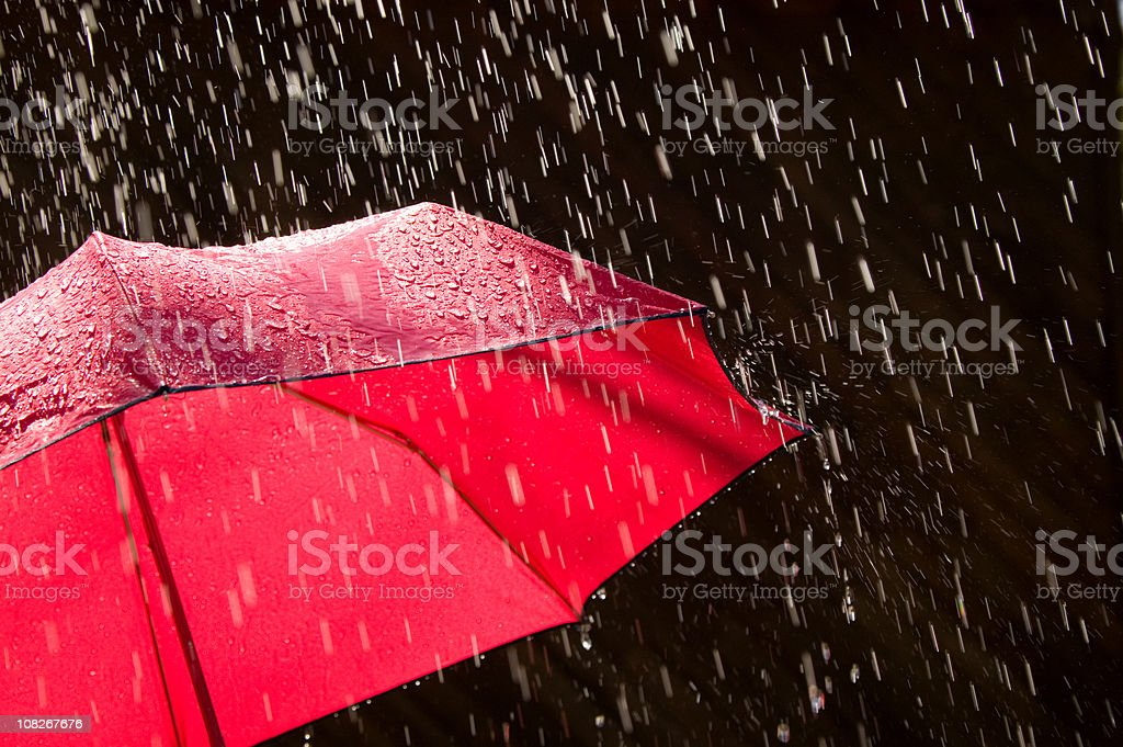 Red Umbrella and Rain Against Black Background stock photo