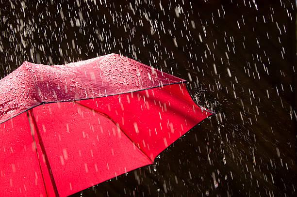 red umbrella and rain against black background - umbrellas stock photos and pictures