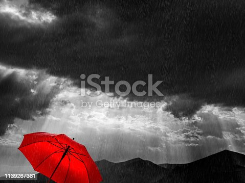 Red umbrella and rainy-sunny weather at nature in Greece.