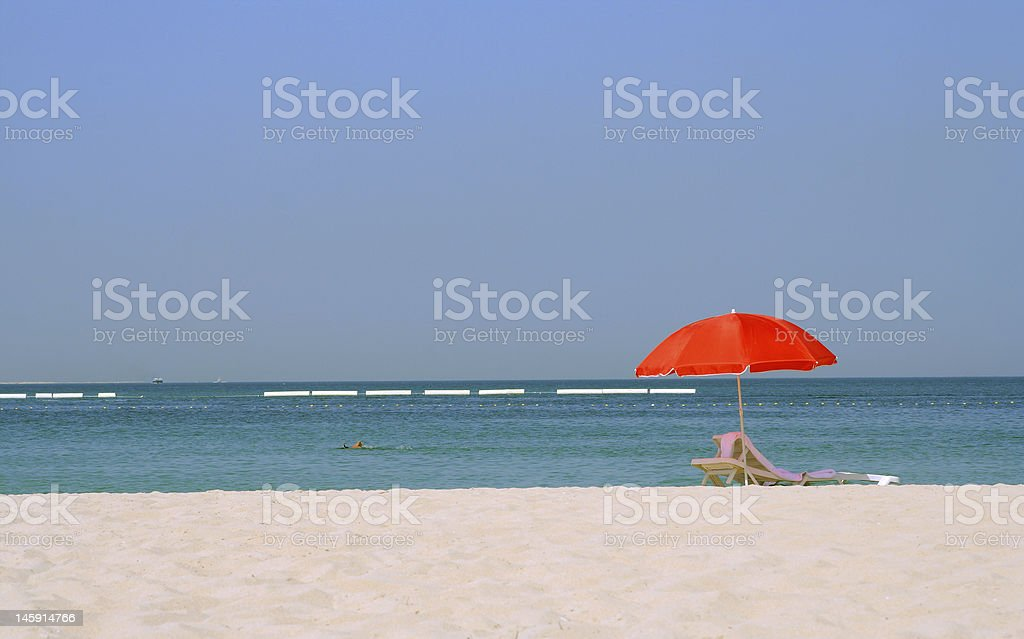 red umbrella on a sand beach at seaside royalty-free stock photo