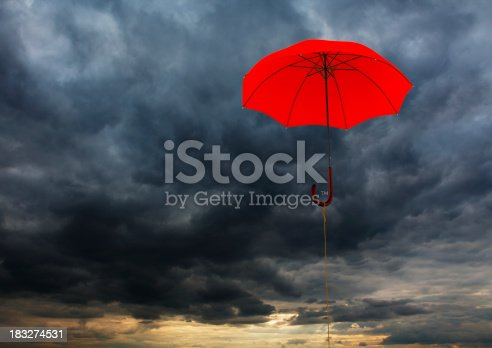 Flying red umbrella against the cloudy sky