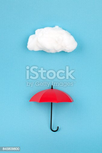 red umbrella under the cloud on sky blue background.