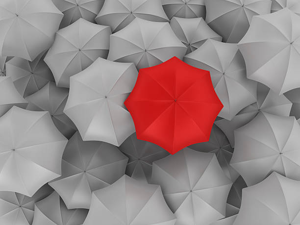 red umbrella with many gray ones - umbrellas stock photos and pictures
