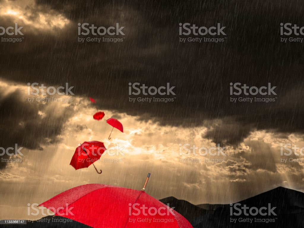Red umbrellas flying in stormy weather and landscape in Greece.
