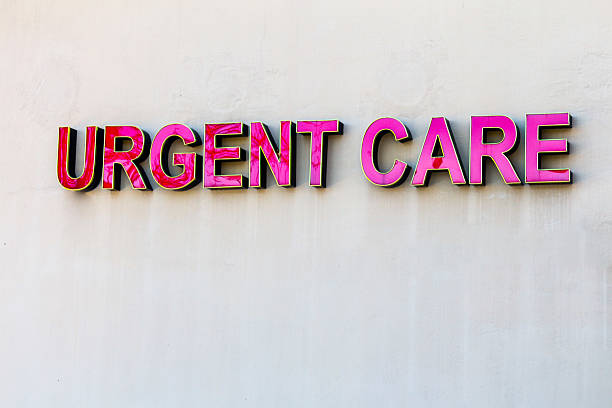 Red urgent care sign on beige wall stock photo