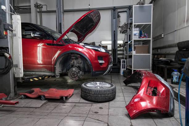 紅色二手車,在電梯上升起一個開放式發動機罩,用於在車輛修理廠修理底盤和發動機,拆下車輪和破損保險杠。汽車服務業。圖像檔