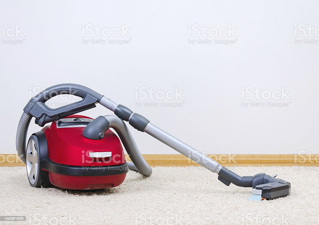 Red vacuum cleaner in empty room. stock photo