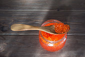 Red vegan caviar from kelp in a glass jar with a wooden spoon on the table. Valuable and healthy product for a healthy diet. Superfood.