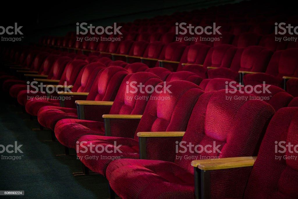 Red velvet armchairs in the empty auditorium stock photo