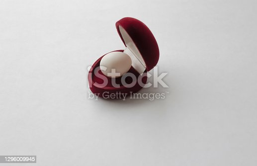 Open Red velvet box for a wedding ring with an egg inside on a white background. Love concept. Valentine's Day.Copy space