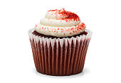 A red velvet cupcake on a white background with icing and sprinkles.