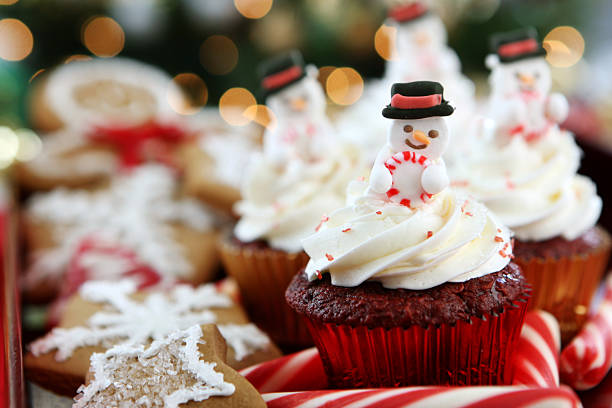 Red velvet cupcakes with marzipan snowman in frosting stock photo