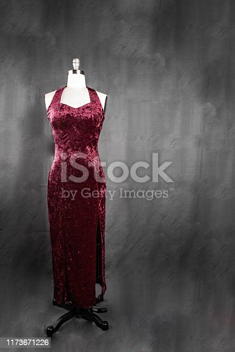 A beautiful red velvet dress on a dress form with a gray background.