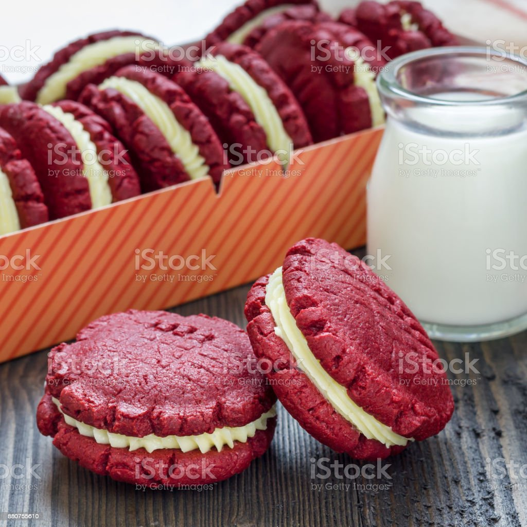 Red velvet sandwich cookies with cream cheese filling on wooden table, square format stock photo
