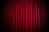 deep red stage curtain in spotlight, background texture with space for text