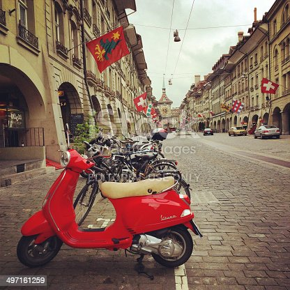 Berne, Switzerland - May 3, 2014: Red Vespa parked in old city of Berne, Switzerland, Kramgasse, main street in old Berne.