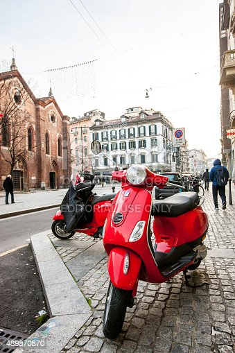 Milan, Italy - December 22, 2014: Red Vespa parked on Milan street. People walking on the street.