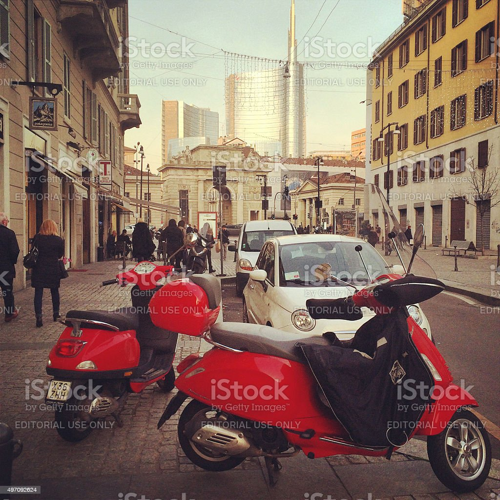 Red Vespa parked on Milan street stock photo