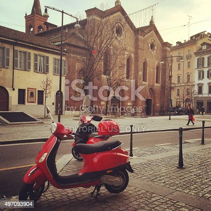 Milan, Italy  - December 22, 2014: Red Vespa parked on Milan street. People walking on the street.