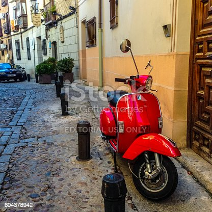 Toledo, Spain - December 23, 2013: Red Vespa parked on Toledo street, Spain