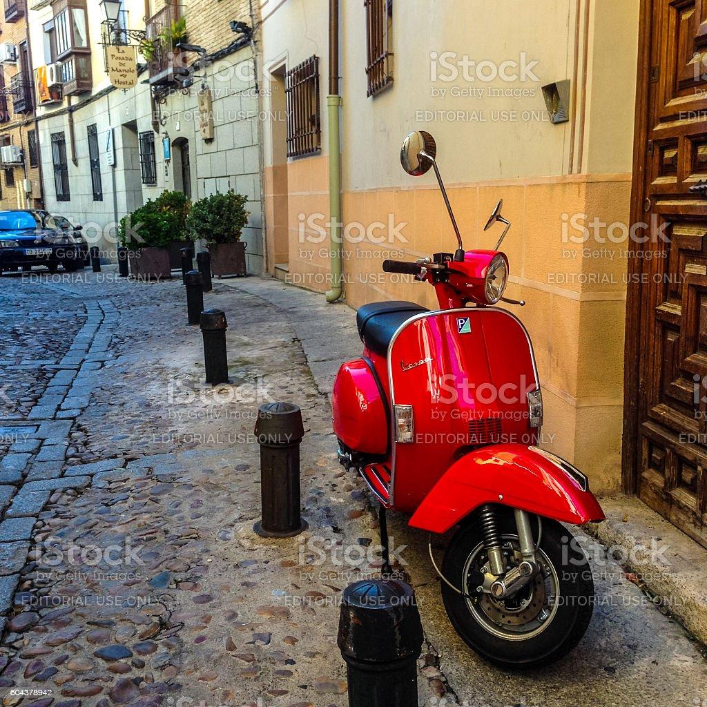 Red Vespa parked on Toledo street, Spain stock photo
