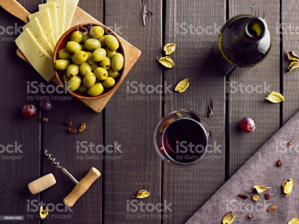 Red vine served with green olives and cheese. stock photo