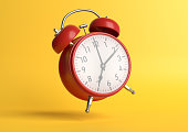 istock Red vintage alarm clock falling on the floor with bright yellow background in pastel colors 1212889961