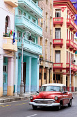 Vintage American cars speeding in front of dilapidated buildings in traditional colonial style, Havana, Cuba, 50 megapixel image