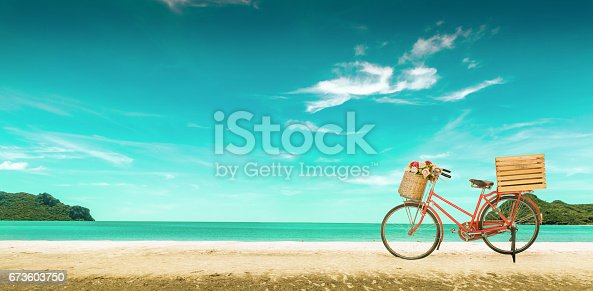 istock Red vintage bicycle on white sand beach over blue sea and clear blue sky background, spring or summer holiday vacation concept,vintage style. 673603750