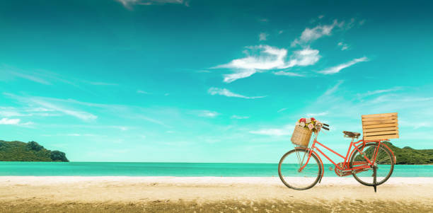 Red vintage bicycle on white sand beach over blue sea and clear blue sky background, spring or summer holiday vacation concept,vintage style. stock photo