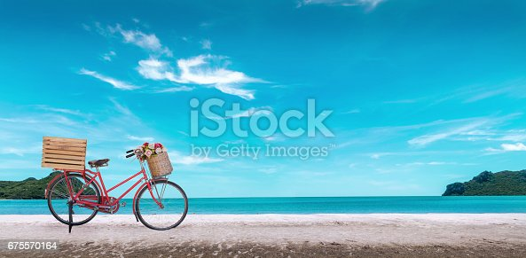istock Red vintage bicycle on white sand beach over blue sea and clear blue sky background, spring or summer holiday vacation concept. 675570164